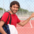 Tennis player stood by outdoor court - Stock Photo