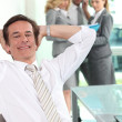 Relaxed executive in the office with his colleagues in the background — Stock Photo