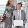 Pair of confident executives with laptop computer — Stock Photo