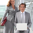 Stock Photo: Pair of confident executives with laptop computer