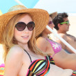 Young woman in a straw hat sunbathing on the beach with friends — Stock Photo #7424049