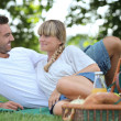 Young couple having a picnic in the park - Stock Photo