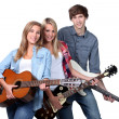 Three teenage guitar players — Stockfoto