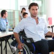 Man using a wheelchair in an office environment — Stock Photo