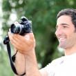 szczęśliwy, zrelaksowany człowiek patrząc na ekran swojego aparatu dslr jak on ma ph — Zdjęcie stockowe