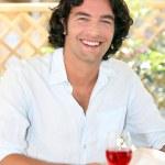 Smiling man enjoying a glass of rose — Stock Photo