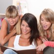 Stock Photo: Young women looking at photos