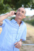 Middle-aged man outdoors with mobile telephone — Stock Photo