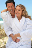 Portrait of couple on dunes in towelling robes — Stock Photo