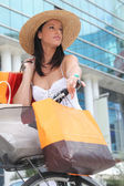 Summer in the city: woman with shopping bags and bicycle — Stock Photo