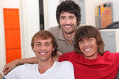 Three smiling lads sitting on a sofa — Stock Photo