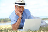 Senior man lying on the grass in the sunshine using a laptop computer — Stock Photo