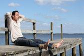 Homem descalço, sentado em um píer de madeira, desfrutar do sol — Foto Stock