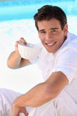 Handsome young man drinking from a china bowl — Stock Photo