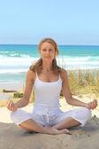 Woman meditating on the beach — Stock Photo