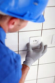 Electrician fitting plug socket — Stock Photo