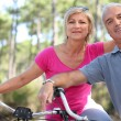 Portrait of mature couple on bicycle — Stock Photo