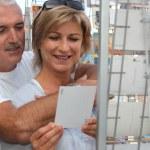 Senior couple on vacation buying post cards — Stock Photo #7430300