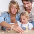A cute little girl playing dominos with her parents. — Stock Photo