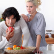A couple in the kitchen, the man is eating an apple — Foto de Stock