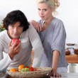 Foto Stock: A couple in the kitchen, the man is eating an apple