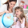Mother and daughter looking at a globe with a magnifying glass — Stock Photo