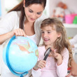 Stock Photo: Mother and daughter looking at a globe with a magnifying glass
