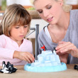 Mother an daughters playing with small penguins figurines — Stock Photo