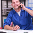 Blue collar worker in his office and on the phone — Stock Photo