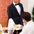 Waiter serving a meal in a restaurant — ストック写真