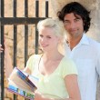 Couple near an iron gate and old stone walls, the woman is holding a guideb — Stock Photo