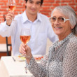 Grandmother and young man drinking rose wine — Stock Photo