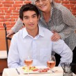A young man and an old woman at the restaurant posing for the camera — Stock Photo