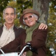 Elderly couple on a bike ride in the forest — Stock Photo #7434297