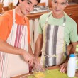 A young man and his grand father wearing aprons and making a cake — Stock Photo #7434642