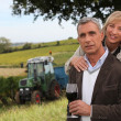 Couple drinking wine in a vineyard — Stockfoto