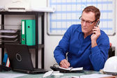 Mechanic on phone in office — Stock Photo