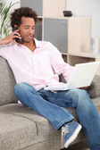 Man sitting on sofa with laptop and mobile telephone — Stock Photo