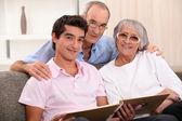 Family looking at photo album — Stock Photo