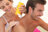 Couple applying suncream — Stock Photo