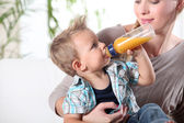Child drinking juice in his mother's lap — Stock Photo