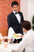 Waiter serving a meal in a restaurant — Stock Photo