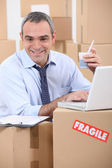 Man amid cardboard boxes — Stock Photo