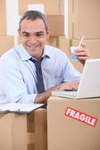 Man amid cardboard boxes — Stock Photo