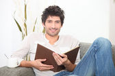 A man reading a book on couch — Stock Photo