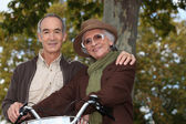 Elderly couple on a bike ride in the forest — Stock Photo