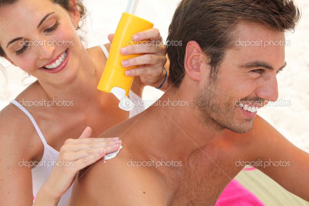 Couple applying suncream  Stock Photo #7431498