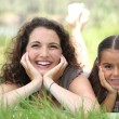 A woman and a little girl lying down in the grass — Stock Photo