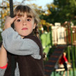 Girl holding onto a rope in a playground — Stock Photo