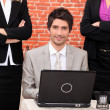 Smiling businessman with laptop surrounded by female co-workers — Stock Photo #7449876